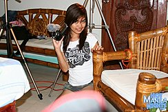 Angie  Squatting Beside Chair Holding Video Camera