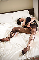 Student lying on bed wearing ripped pantyhose
